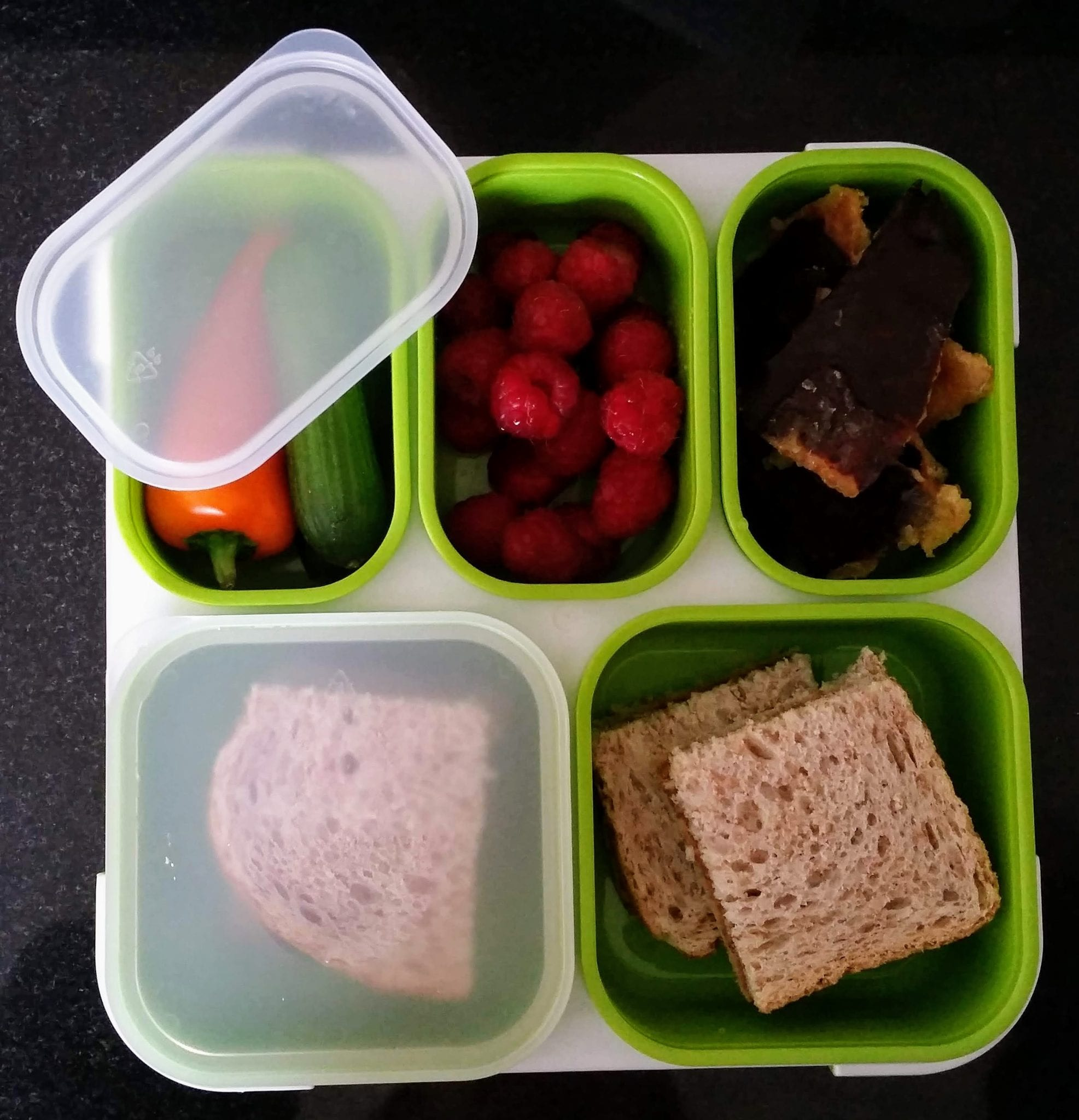 A green 'beta' lunch box containing mini peppers and cucumber, raspberries, chocolate brittle and sandwiches in the various compartments