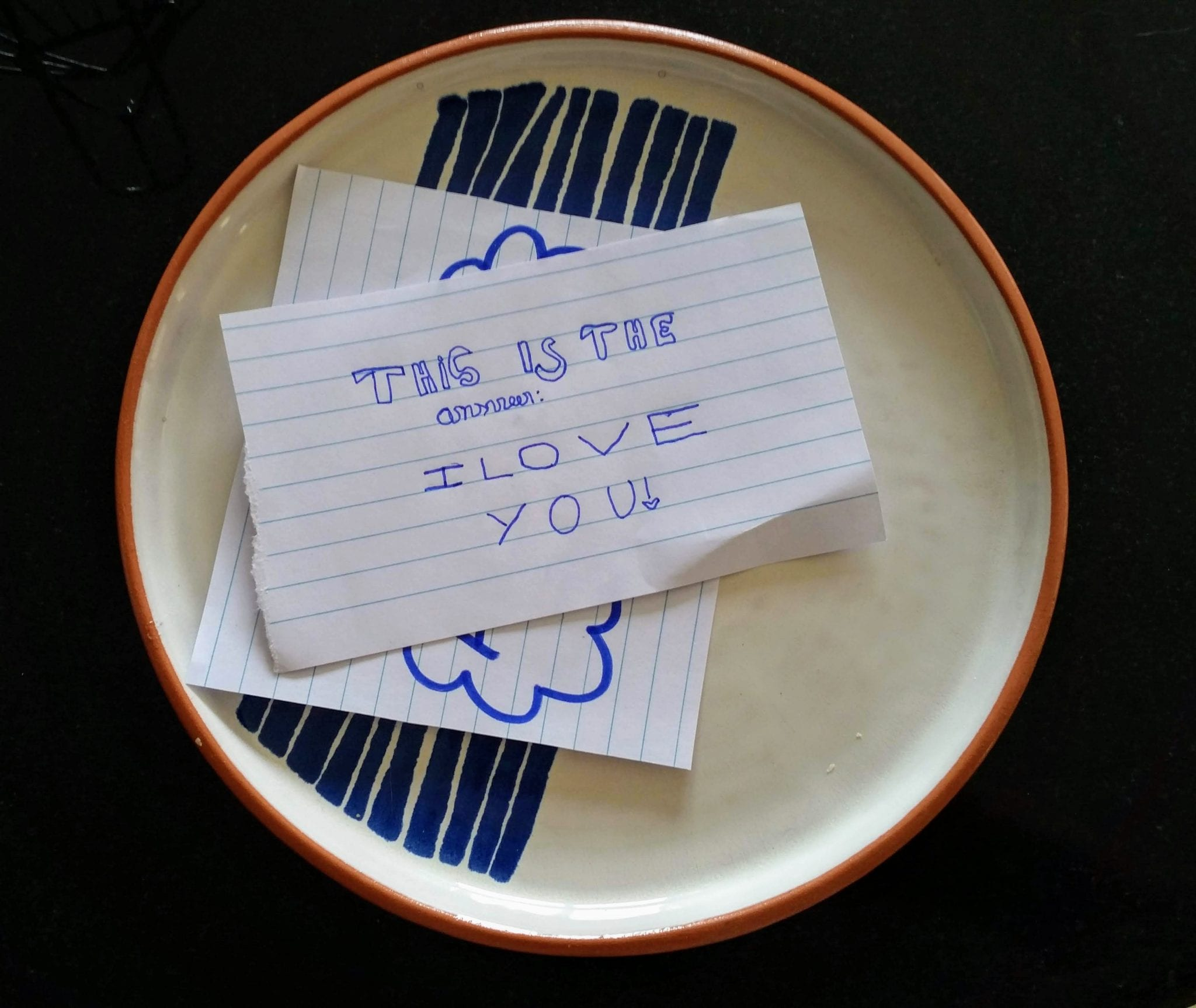 A plate with a piece of paper covering another. The top piece reads 'This is the answer: I love you!'