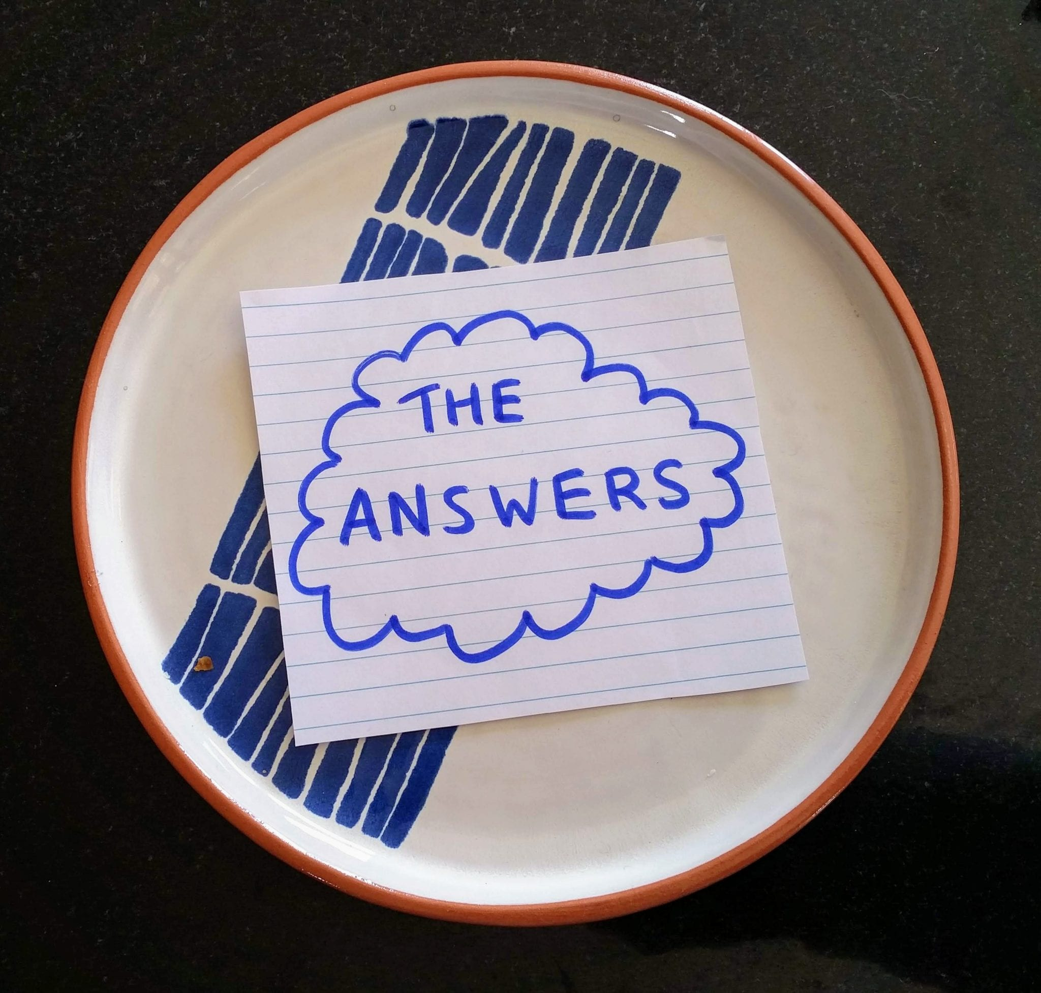 The words 'The Answers' on piece of paper on plate